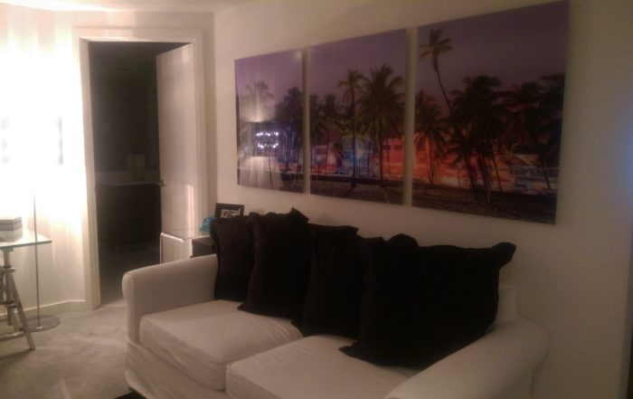 Acrylic print of palm trees in front of multicolored buildings seperated into three panels.