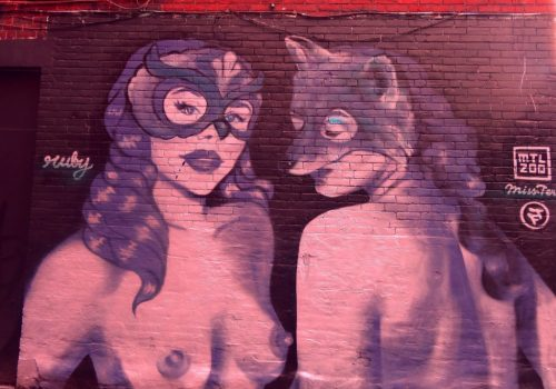 Graffiti art of two topless women wearing masks.