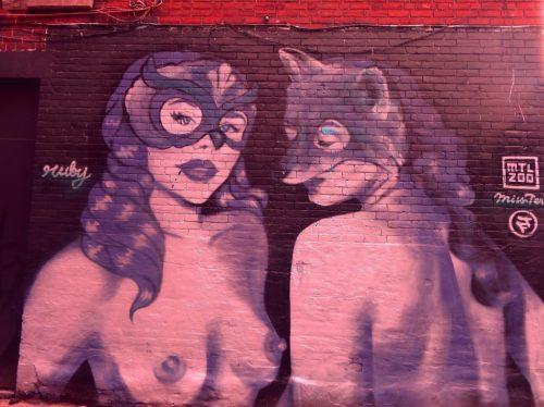 Graffiti art of two topless women wearing masks.