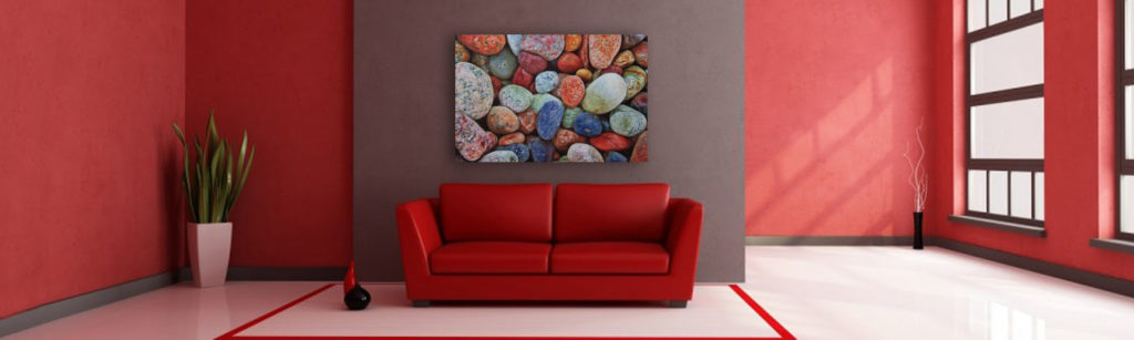 Multi colored rocks on a white washed metal background with gloss.