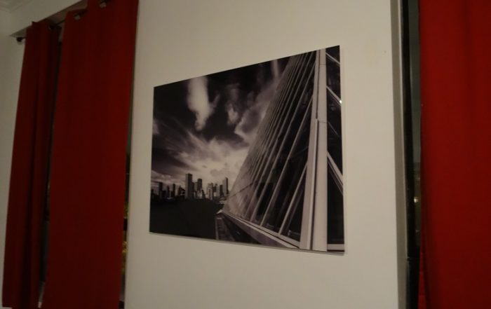 Acrylic print of clouds over buildings in black and white.