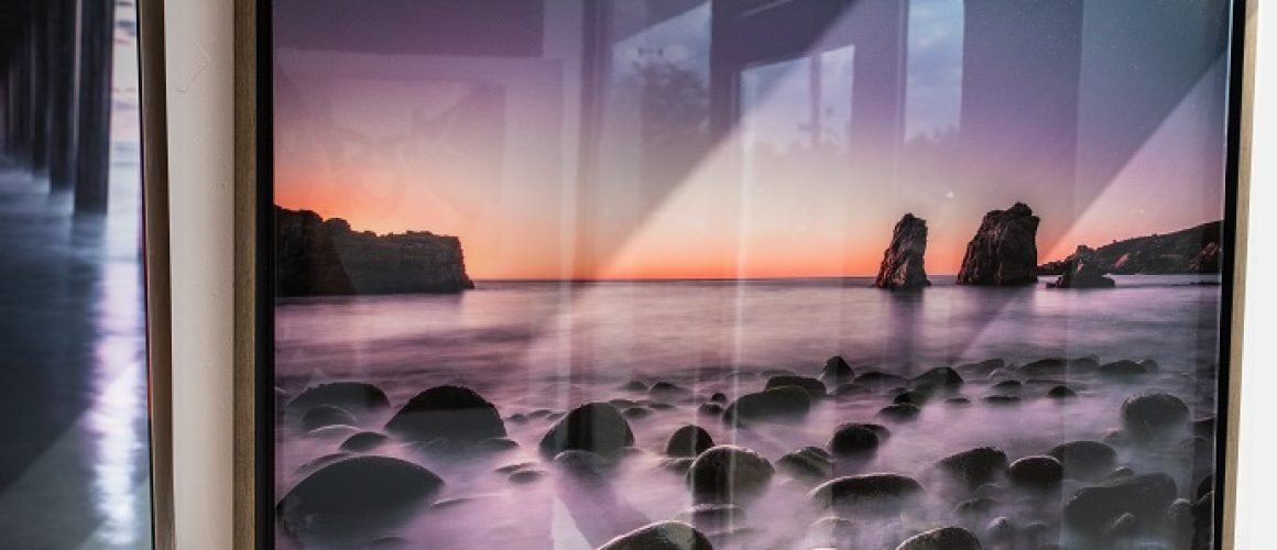 Canvas epoxy print of sunrise over ocean with rocks and fog.