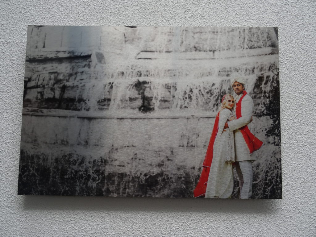 White metal print of wedding couple standing in front of massive rock formation.