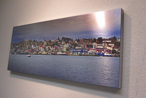 Brushed metal print of multicolored homes in front of a lake.